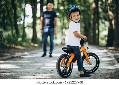 Father teaching his little son to ride a bicycle