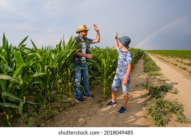 Father is teaching his son about cultivating corn. Corn plantation successfully sown. Farmers in agricultural field.
