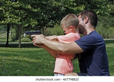 Father teaching his son about gun safety and proper use.