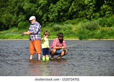 Father teaching his son fishing against view of river and landscape. Fishing in river. Summer weekend. Father and son fishing