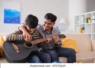 Father teaching his son how to play guitar