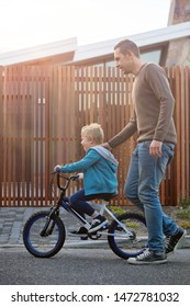 Father teaching his son kid how to ride a bike bicycle cycle outside their house in the suburbs
