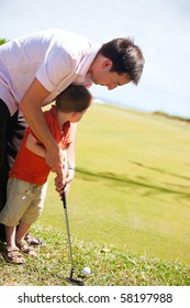 Father teaching his son to play golf