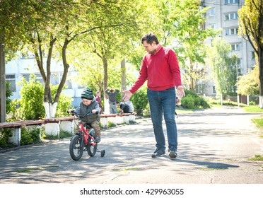 Father teaching his son to ride a bike. boy learning to ride bicycle. having fun together