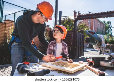 The father teaching his son to use hammer and nails
