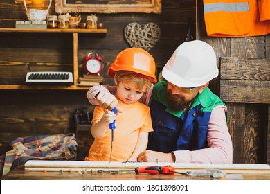 Father is teaching his son to use the screwdriver and hammer. Work with tools construction. Child growth concept