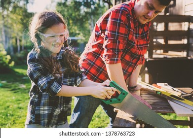 father teaching kid daughter to use tools. Girl helping dad with building work outdoor in summer, country house on background