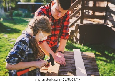 father teaching kid daughter to work with wood outdoor. Dad explaining how to use hammer and build wooden details. Country house on background