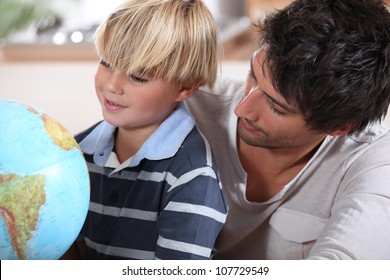 Father teaching little boy about different countries
