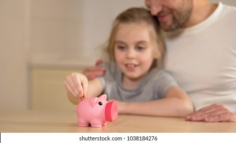 Father teaching little daughter to save money in piggy bank, financial literacy