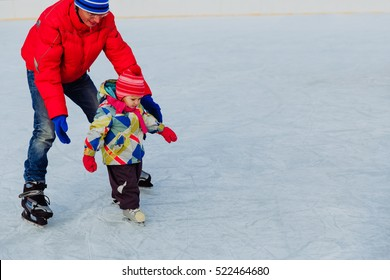 father teaching little daughter to skate in winter