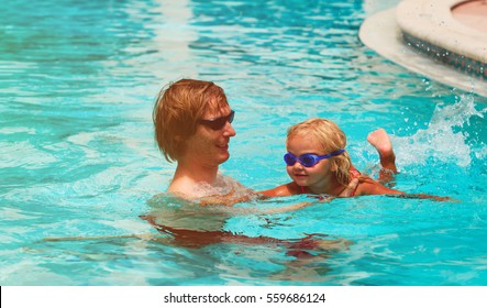 Father teaching little daughter to swim