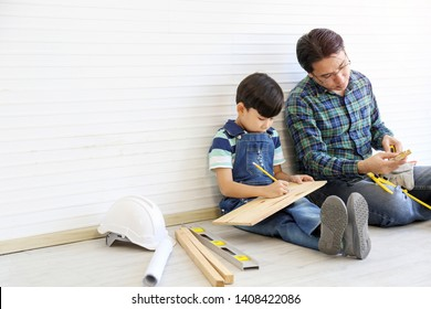 Father teaching son for construction working or renovated house, they wearing casual chess blue shirt and sitting on the floor among wood and safety helmet, happy family relationship concept.