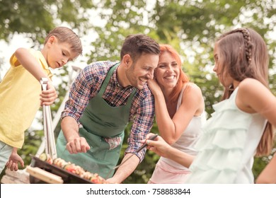 Father teaching son cooking on barbecue with family in background.Leisure, food, people and holidays concept.