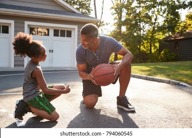 Father Teaching Son How To Play Basketball On Driveway At Home