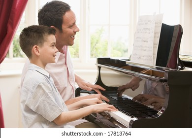 Father teaching son to play piano