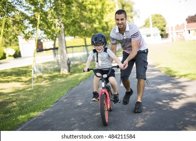 A Father Teaching Son To Ride Bicycle