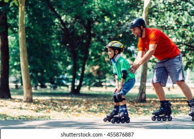 Father teching son roller skating in park