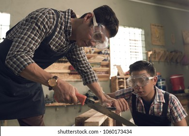 Father and teenage son in goggles working with wood