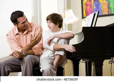 Father with teenage son at home talking together