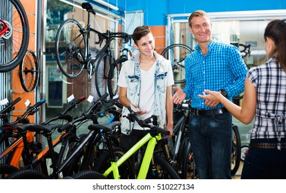 Father with teenager boy asking positive female seller for help in sport bike shop