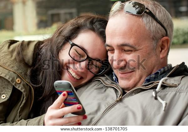 Père et fille adolescente avec la tête dans l'épaule et partageant quelque chose d'amusant sur un téléphone portable
