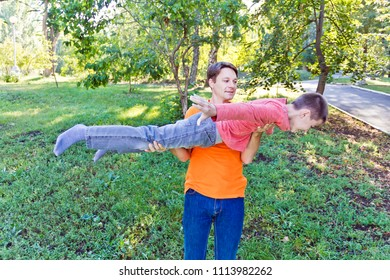 Father and teenager son are playing in summer park