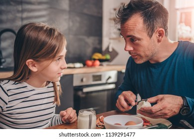 Father telling jokes to her daughter at breakfast