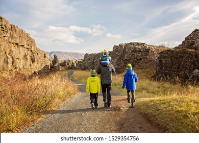 Father with three children, enjoying a sunny day in Thingvellir National Park rift valley, Iceland autumntime