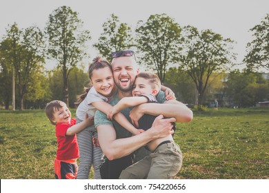 father with three children having fun in the park. hipster style. casual clothes. concept of happy family