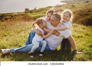 Father with three daughters sitting on the grass on the sea coast in summer. Family concept.