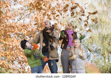 Father throwing autumn leaves in the air