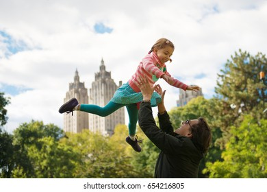 Father Throwing Daughter up in Air