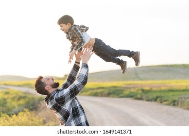 Father throwing his son in the air playing outdoors happy in spring