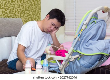 Father tired and asleep  his newborn baby boy with milk bottle sitting on a white couch in living room at home