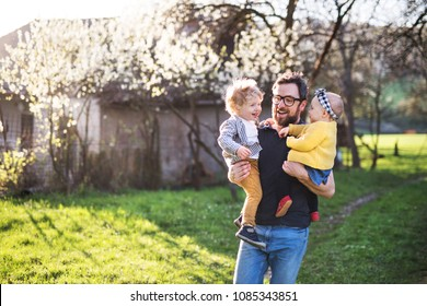 A father with toddler children outside in spring nature.