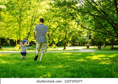 Father and toddler daughter running through the green grass.Back of dad and little child chasing in park.Copy space