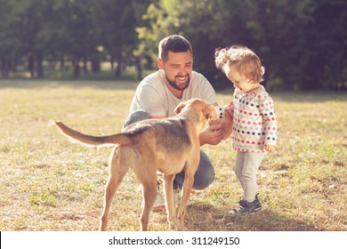 Father and toddler feeding and walking with dog