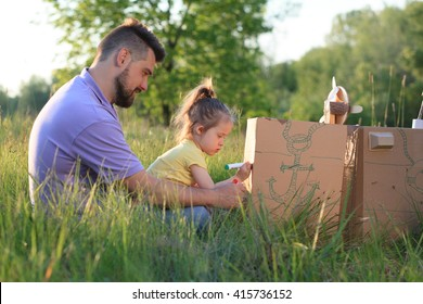 Father and toddler girl playing with paperboard ship in the yard