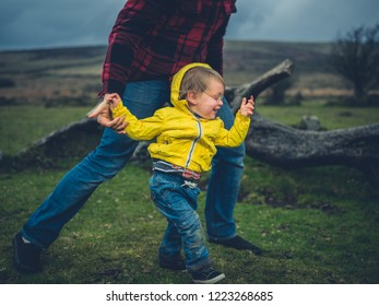 A father and toddler are walking on the moor in the wind