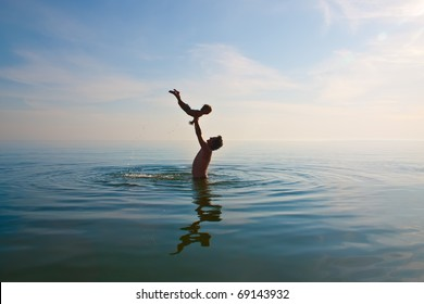 father is tossing up a child in water
