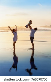 Father tossing high in air baby son, mother jumping by water pool. Happy family walk with fun by sunset black sand beach with sea surf. Active parents, outdoor activity on summer vacation with kids.