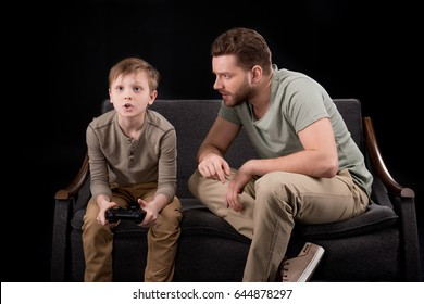 Father trying to talk with little son playing with joystick, family problems concept