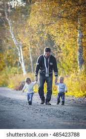 Father with twins boy and girl walking in autumn park