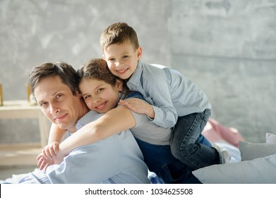 Father of two children. The boy and the girl embrace the father. All have on faces happy smiles..