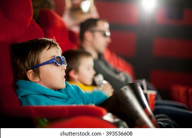 Father and two children, boys, watching cartoon movie in the cinema on 3D