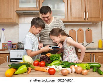 Father and two children reading cooking book and choice dishes. Happy family, girl and boy having fun with fruits and vegetables in home kitchen interior. Healthy food concept.