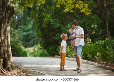 Father with two children walking in a summer park