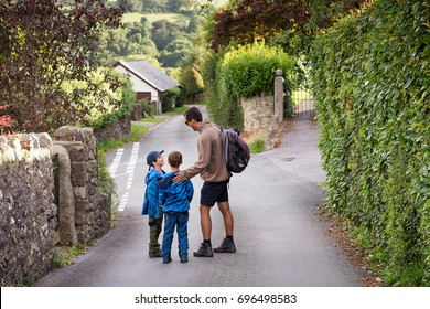 Father with two children walking and talking on a village country road, Devon, England, UK