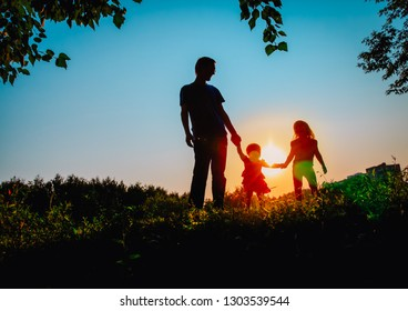 father with two daughters walk at sunset nature
